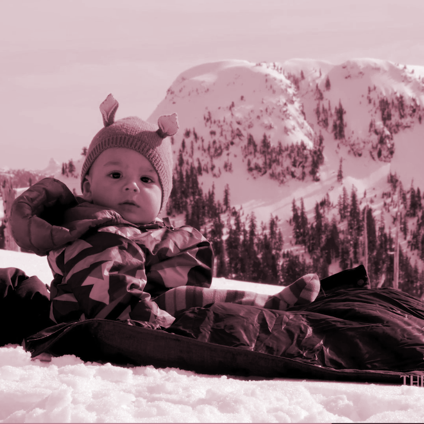 A baby bundled up in a sled